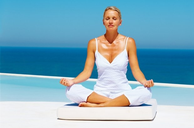 Tanned woman meditating on beach