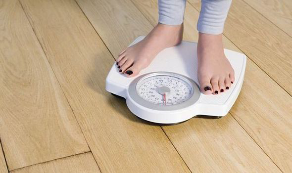 Woman weighing herself on scales